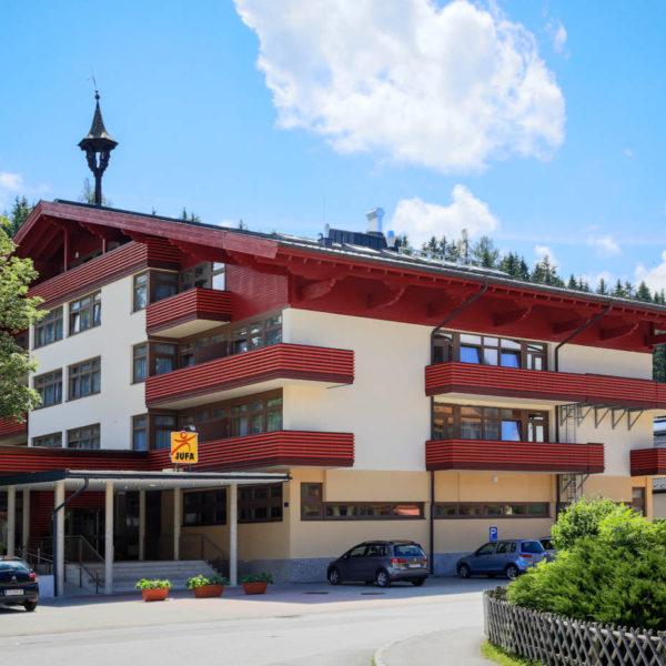 Sie sehen eine Außenansicht vom JUFA Hotel Altenmarkt im Sommer. JUFA Hotels bietet erholsamen Familienurlaub und einen unvergesslichen Winter- und Wanderurlaub.