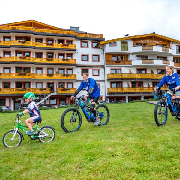 Sie sehen eine Familie beim Mountainbiken in Saalbach vor dem JUFA Alpenhotel Saalbach****. Der Ort für erholsamen Familienurlaub und einen unvergesslichen Winter- und Wanderurlaub.
